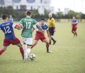 Two soccer players battle for the ball in a soccer game